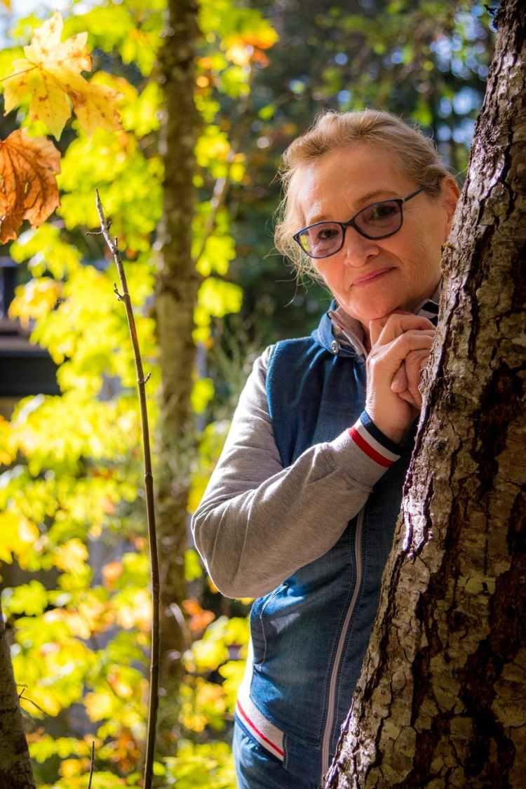 woman standing behind tree
