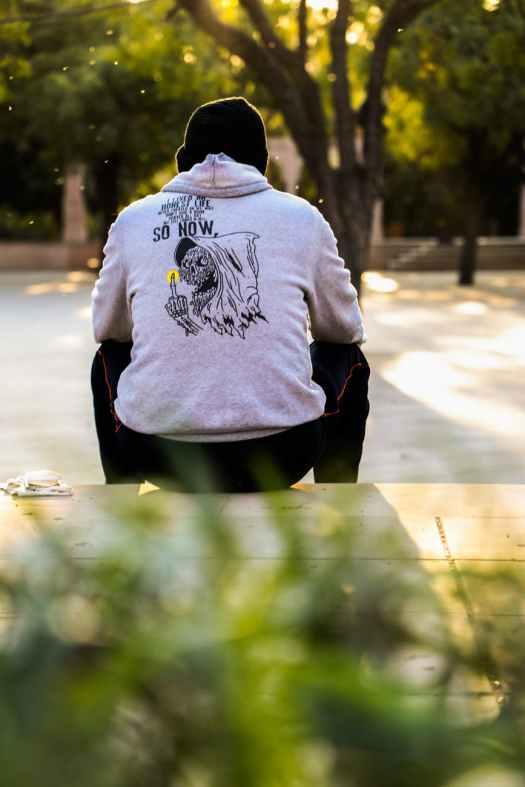 man sitting alone on pavement